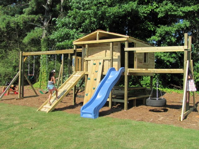 8x8 model as shown $4775.00 including Swings, Trapeze Bar with Rings, Wooden Ramp with Rope, Wooden Bridge with Tire Swing, rock Climbing Wall, Monkey Bars, and Picnic Table
