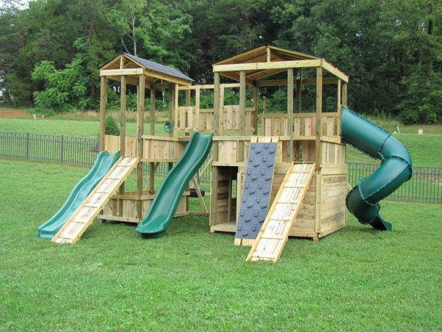8x8 Mammoth and 4x8 Fox's Den models as shown $9195 including 10' Wave Slide, 13' Wave Slide, Enclosed Turbo Slide, Shingled Roofs, Rock Climbing Wall, Soft Grip Swings, Wooden Ramps with Rope, Wooden Bridge