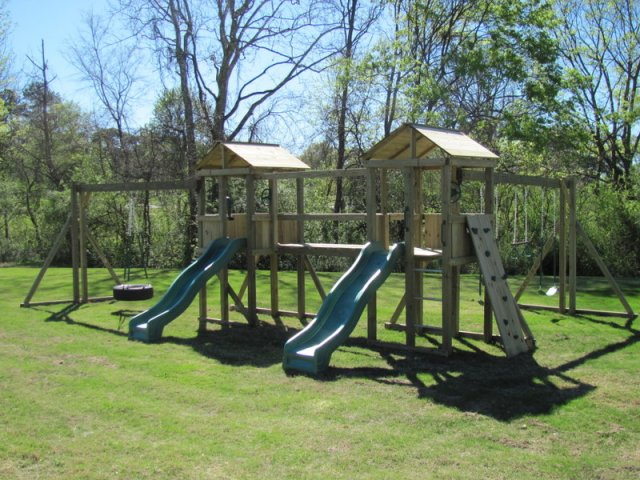 2 4x4 Jungle House models as shown $2550 including Wooden Roofs, 2 Slides, Rock Climbing Wall, Soft Grip Tire Swing, Soft Grip Swings, Trapeze Bar with Rings, Periscope, and Wooden Bridge