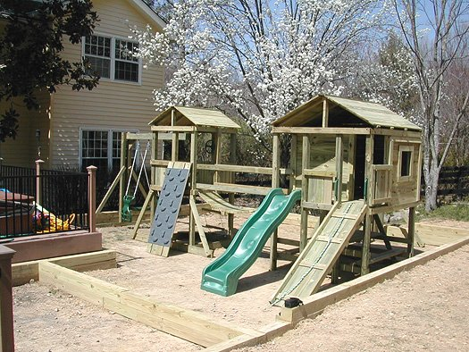 $4375 4x4 Jungle House and 6x6 Bear's Den model with grey rock wall,swings, glider horse,picnic table. WILL HAVE SOLID BRIDGE. Swinging bridge no longer available.